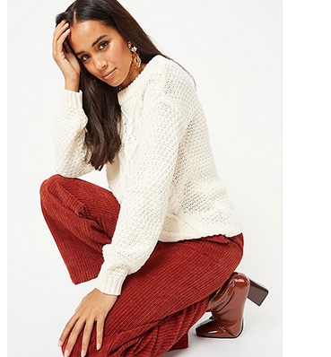 Woman crouching down wearing a cream knitted jumper and burnt orange corduroy trousers with brown heels
