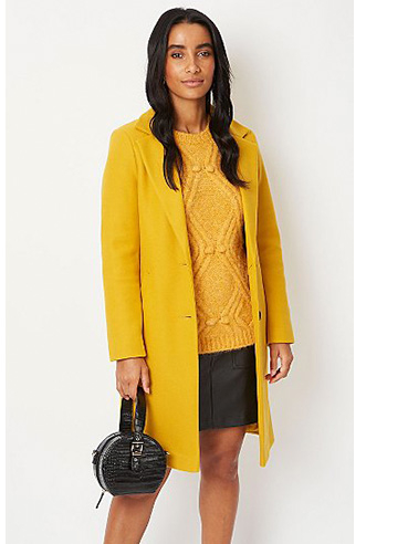 Woman wearing an ochre coloured jumper with matching longline coat and black faux leather skirt with matching handbag
