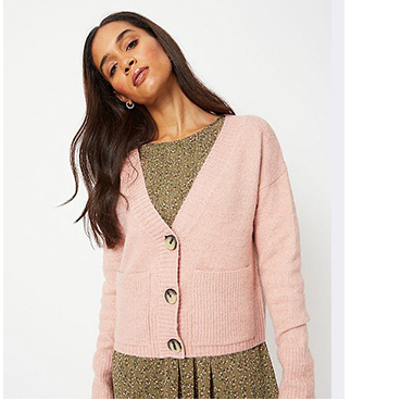Woman wearing pink V-neck cardigan over a patterned khaki dress