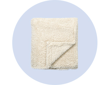 Snuggle up in this cream teddy throw