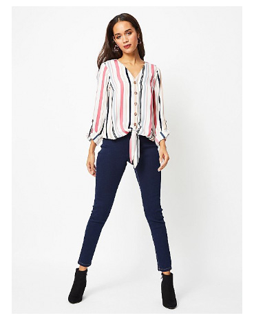 Woman wearing multicoloured striped buttoned knot front blouse, jeans and black ankle boots