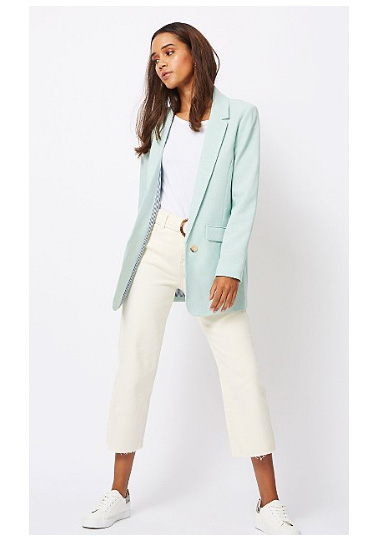 Woman wearing white top, white jeans and white trainers with a mint green blazer