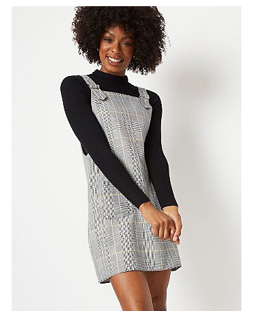 Woman wearing grey check pinafore dress over black long sleeve top