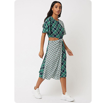 Woman wearing green check cut out waist midi dress