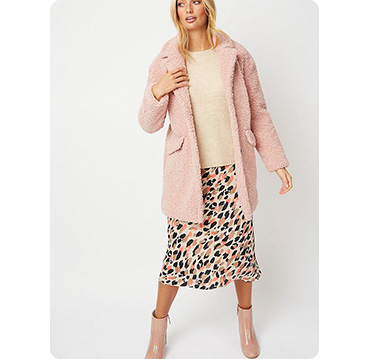 Woman wearing pink teddy fleece coat, beige top and animal print skirt with pink boots