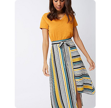Woman wearing orange top with yellow stripe print asymmetric midi skirt
