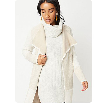 Woman wearing cream roll neck cable knit jumper and matching coat