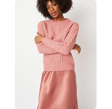 Woman wearing pink knitted jumper and satin look pink skirt