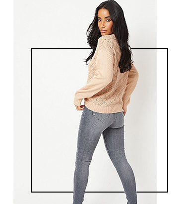 Woman looking back at camera wearing a jumper and jeans