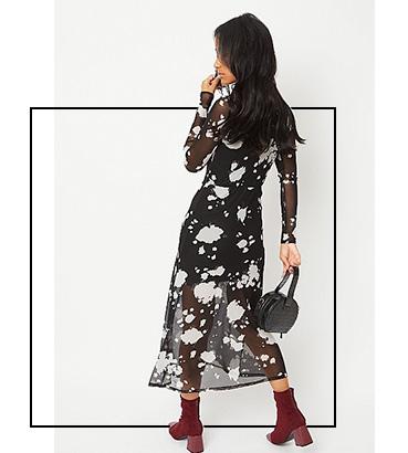 Woman wearing a black splatter mesh maxi dress and burgundy heeled boots carrying a black handbag