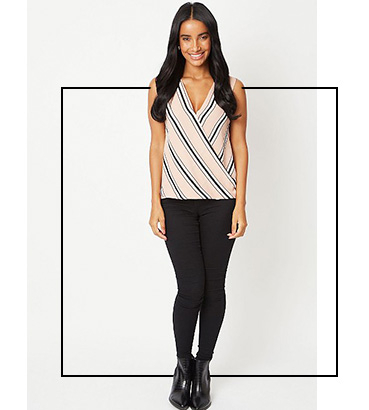 Woman wearing a pink striped wrap style V-neck blouse with black trousers and matching boots