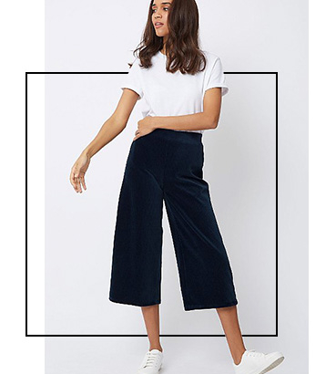 Woman wearing a white T-shirt with navy ribbed texture culottes and white trainers