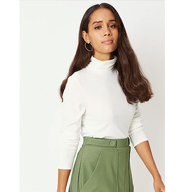 Woman wearing white roll neck jumper and green skirt