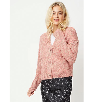 Woman wearing pink cardigan over a white top and a black dotted skirt