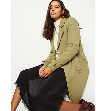 Woman wearing a green trench coat over a jumper and black skirt