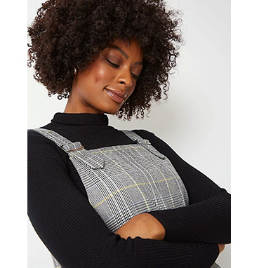 Woman wearing check pinafore over a black jumper
