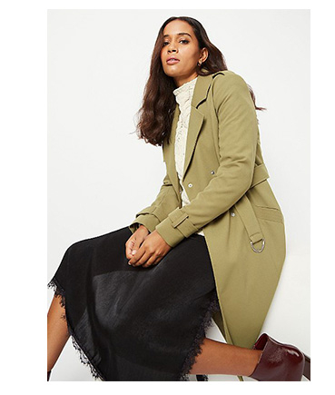 Woman wearing olive green trench coat, cream jumper, black skirt and boots