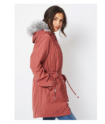 Woman wearing dusty pink faux fur removable inner longline parka