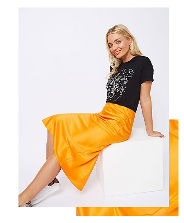 Match a vibrant orange satin look midi skirt with a black top