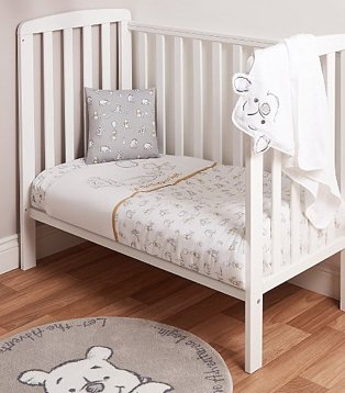 White baby nursery features white cot bed with Disney Winnie the Pooh bedding set and Disney Winnie the Pooh rug.