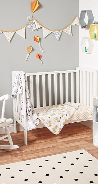 White and grey baby nursery features white Rafferty cot bed with Disney Lion King bedding, bunting and monochrome polka dot rug.