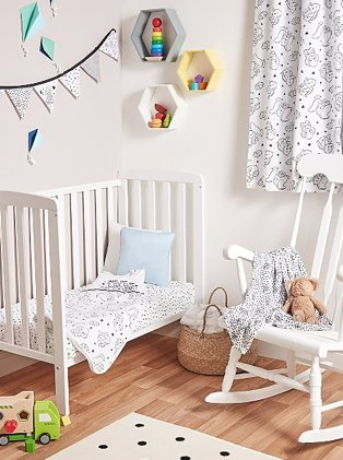 White baby nursery features white Rafferty cot bed with Disney Dumbo bedding, white rocking chair, bunting and monochrome polka dot rug.