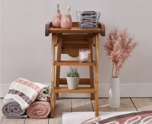 Wooden ladder table features pink rainbow print dispenser and tumbler set, grey hand towels in wire basket, pink candle and artificial potted plant with selection of grey, pink and cream towels and artificial plant on floor.