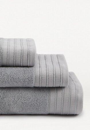 Stack of light grey hand towel, bath towel and bath sheet.