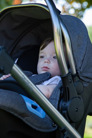 Baby lays in pushchair.