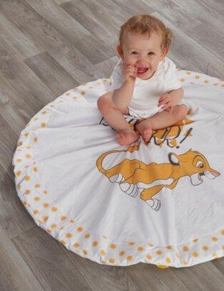 Smiling baby wearing white bodysuit sits on Lion King circle blanket.