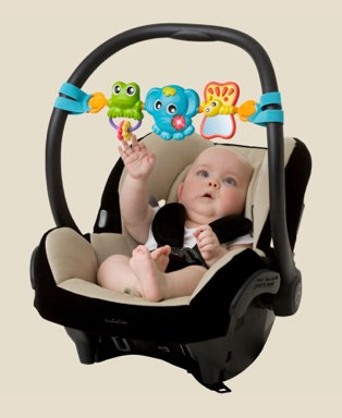 Baby lays in black and cream car seat playing with frog, elephant and butterfly mobile.