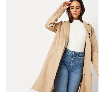 Woman wearing a cream top, jeans and beige longline jacket