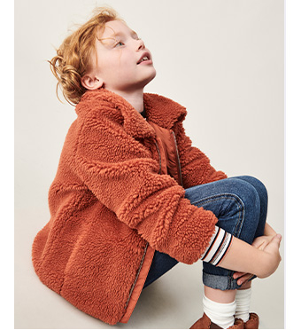 Child sitting down wearing a brown borg coat and jeans