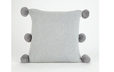 Light grey textured cushion with pom poms