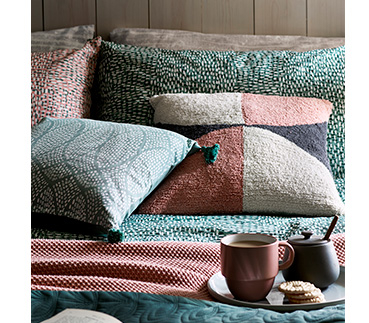 Textured cushions on a bed with a mug and sugar pot
