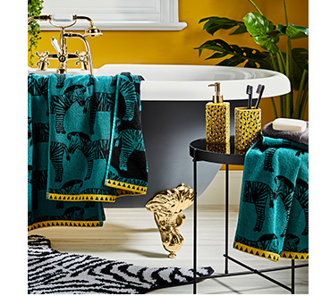 Bathroom featuring green zebra print towels and yellow leopard print accessories