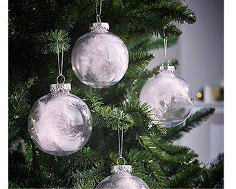Close up of Christmas tree with clear baubles containing white feathers