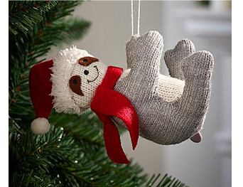 Knitted sloth hanging from a Christmas tree wearing a red scarf and Santa hat