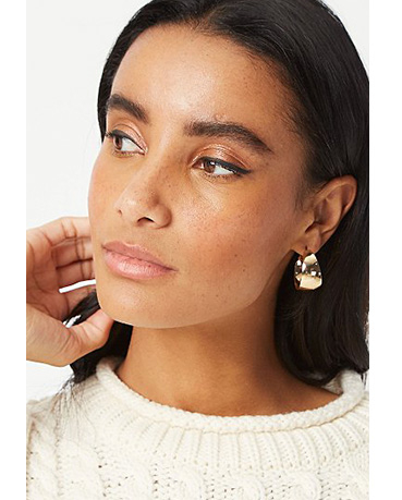 Close up shot of woman looking to the side wearing a cream jumper and hoop earrings