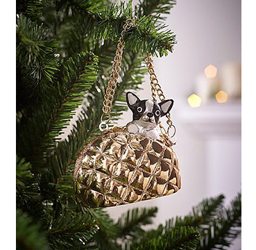 Dog in a gold handbag decoration hanging on a Christmas tree