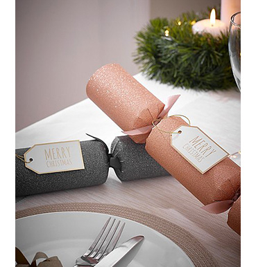 Rose gold and grey glitter Christmas crackers on a table