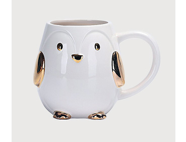 White penguin mug with gold tone features