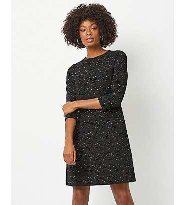 Woman in black shimmering knitted dress