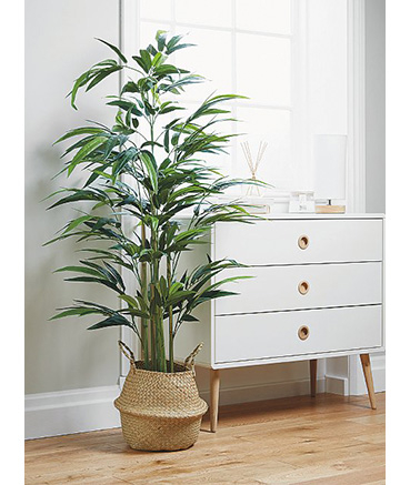 Large artificial plant in wicker planter next to a set of white drawers