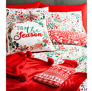 Red Christmas bedding with matching cushions, a red throw and a red hot water bottle