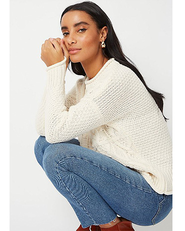 Woman crouched down wearing a cream knitted jumper and blue jeans