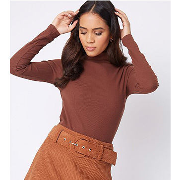 Woman wearing a brown long sleeve top with a brown cord skirt