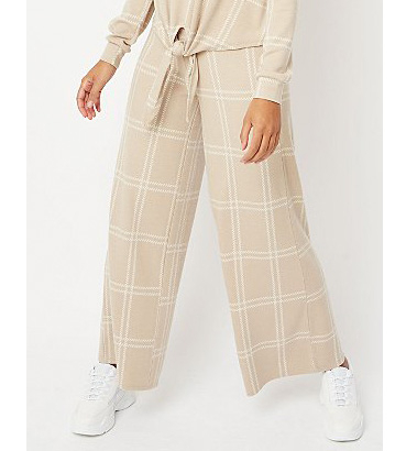 Close up shot of woman wearing cream checked wide leg trousers with trainers