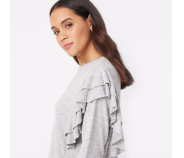 Woman standing to the side wearing a grey frill jumper