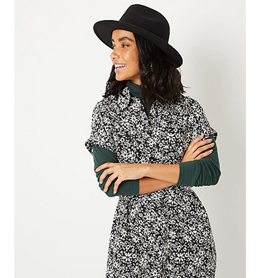 Woman wearing a green long sleeve top, floral dress and black hat
